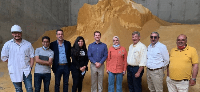 9 People Standing in Front of Pile of Substance