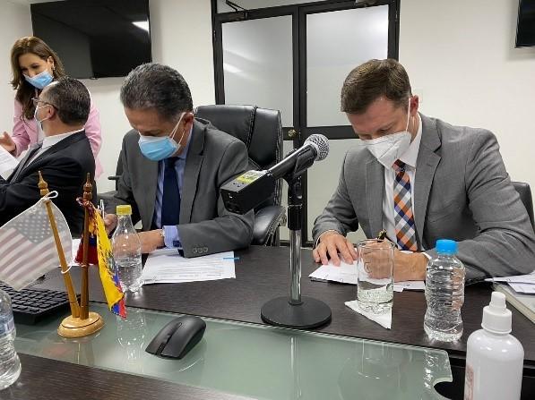 Men signing document